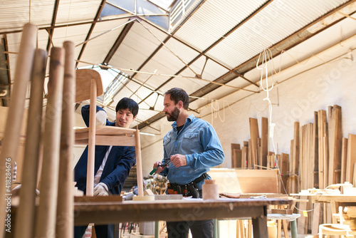 Canvas-taulu Cabinet maker trainee and trainer build chairs