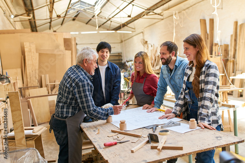 Obraz Senior craftsmen as trainers with trainees - fototapety do salonu