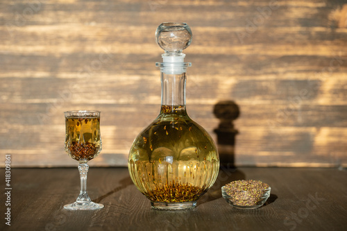 Fotografiet Homemade birch buds tincture in a glass bottle and a wine crystal glass on a woo
