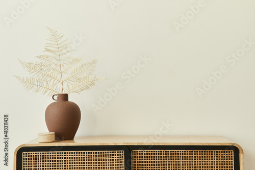 Modern scandinavian home interior with design wooden commode, dried leafs in ceramic vases and personal accessories in stylish home decor. Template. Copy space. White walls.
