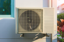 Condenser Unit Or Compressor Outside Home Or Residential Building. Unit Of Central Air Conditioner (AC) Or Heating Ventilation Air Conditioning System (HVAC). Electric Fan And Refrigerant Pump Inside.
