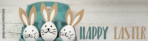 Obraz Happy Easter background banner panorama greeting card -Close-up from white painted eggs and easter bunny in green turquoise egg carton on rustic white vintage shabby wooden table - fototapety do salonu