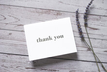 Thank You Card On Wooden Table With A Pair Of Lavender Flowers. Elegant Minimalist Composition. Special Thank You Note.