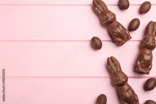 Chocolate Easter bunny and eggs on pink wooden table, flat lay. Space for text © New Africa