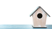 Beautiful Bird House On Light Blue Wooden Table Against White Background, Space For Text