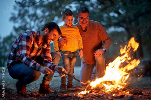 Boy with father and grandfather enjoying in campfire Fototapet