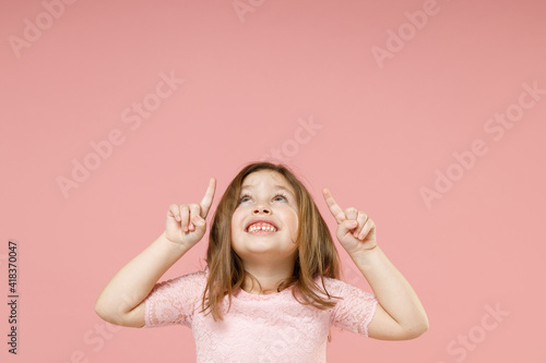 Fototapeta Little kid girl 5-6 years old in dress point fingers up on workspace commercial promo area mockup copyspace isolated on pastel pink background child studio portrait. Mother's Day love family concept. obraz