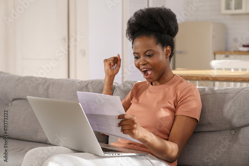 Foto Excited millennial African American woman sitting on couch at home, holding and reading paper document, feel euphoric