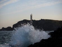 Sea Wave Water Smashing Hitting Breaking On Rocky Shore At Cliff Coast Of Punta Frouxeira Lighthouse Tower Galicia Spain