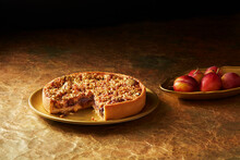 Still Life With Plum And Almond Tart On Gold Plate, Christmas Dessert