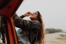 Young Woman Next To Recreational Vehicle At Beach, Jalama, California, USA