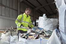 Worker Sorting Out Old Circuit Boards For Recycling In Recycling Factory