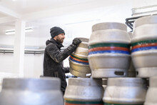 Brewer Stacking Barrels In Small Brewery
