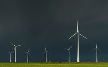 Field Landscape With Dramatic Sky Behind Wind Farm And Traditional Windmill In North Netherlands, Near Waddensea Dyke