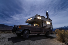 Woman Enjoying View On Top Of Campervan In Desert, Sierra Nevada, Bishop, California, USA