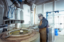 Engineer Dipping Components Into Molten Salt In Engineering Factory