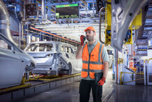 Composite Image Of Worker Using Walkie Talkie In Car Factory