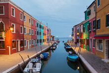 Moored Boats On Canal Lined With Colourful Stucco Houses And Shops At Dusk, Burano Island, Venetian Lagoon, Venice, Veneto, Italy