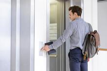 Businessman Pressing Button To Open Elevator Doors