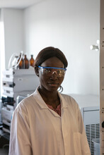 Young Female Scientist Wearing Safety Glasses In Laboratory, Portrait