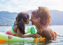 Mother Rubbing Noses With Daughter On Inflatable Frog In Lake