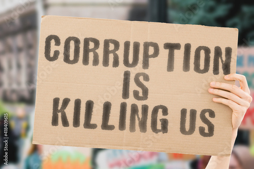 Fotografie, Obraz The phrase  Corruption is killing us  on a banner in hand with blurred background