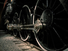 Close Up Steam Locomotive Wheels, Connecting Rods, And Coupling Rods At Night On Tracks And Ballast Nobody