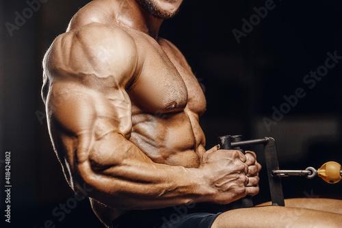 Obraz muscular bodybuilder fitness men doing arms exercises in gym - fototapety do salonu