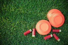 Clay Disc Flying Targets And Shotgun Shells On Green Grass Background ,Clay Pigeon Target