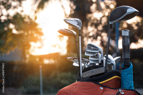 Golf bag and golf clubs placed on golf course against sunset background