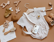 Flat Lay Composition With Girl Bodysuit, Wooden Camera And Toys. Newborn Clothes, Baby Staff, Baby Shower. Top View, Flat Lay