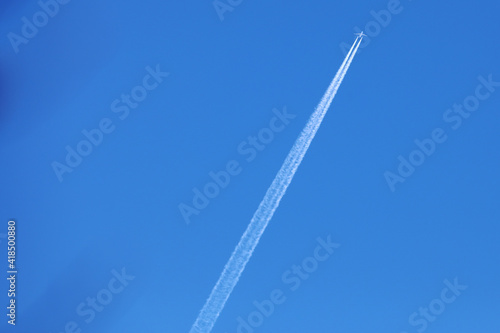Aircraft with condes stripes against a blue sky Fotobehang