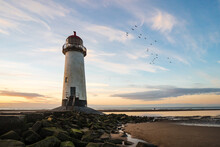 Beautiful Lighthouse By Sea Golden Hour Sunset With Rocks Leading To Stairs As Ocean Tide Comes In.  Birds Flying Out To Horizon Sun Reflecting In Water Pools Of Old Abandoned Amazing Coastline Beach
