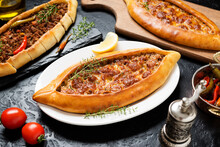 Traditional Turkish Cuisine. Assorted Turkish Pizza. Pide With Ground Beef And Pide With Cheese On Black Stone Background.