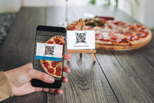 Women's Hands Using The Phone To Scan The Qr Code To Order Pizza. Scan To Get Discounts Or Order For Pizza.