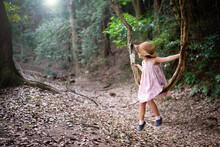 森の中で蔓をブランコにして遊ぶ少女