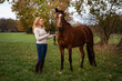 canvas print picture - Eine hübsche langhaarige, lockige, blonde Frau kuschelt mit ihrem Pferd