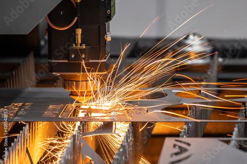 Obraz The fiber laser cutting machine cutting  machine cut the metal plate. The hi-technology sheet metal manufacturing process by laser cutting machine. - fototapety do salonu