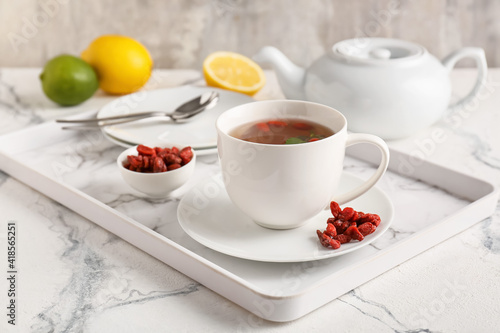 Cup with goji tea on light background © Pixel-Shot