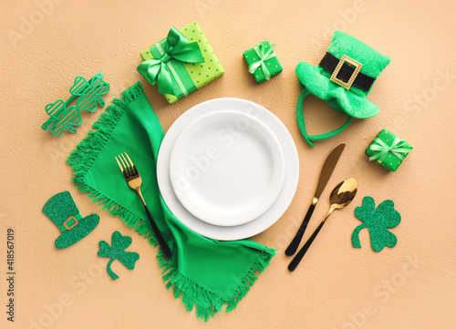 Beautiful table setting for St. Patrick's Day celebration on color background © Pixel-Shot