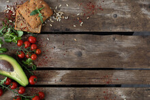 Copy Space. On A Wooden Background, On The Left, Cherry Tomatoes, Avocado, Garlic Bun, Herbs And Sunflower Seeds Are Laid Out With Vegetables. Rustic Style Of Healthy Eating