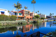 A Gorgeous Shot Of The Still Lush Green Water Of The Canal With Lush Green Trees And Plants Reflecting Off The Water With Homes Along The Canal At The Venice Canals In Venice California