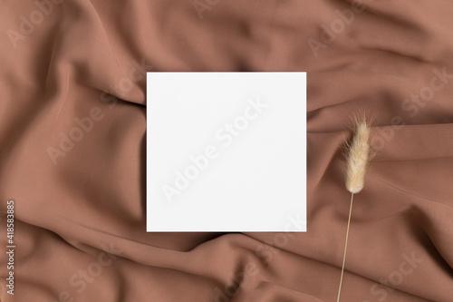 Fototapeta Square invitation card mockup with a lagurus on a textile. obraz