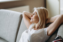 Satisfied Mature Caucasian Woman Is Relaxing On The Sofa At Living Room At Home. Middle Aged Blonde Woman Enjoying Weekend Or Leisure, Sits On Sofa, Looks Away And Dreams About Vacation