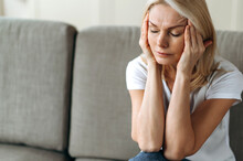 Headache Or Stress. Middle Aged Blonde Woman Sits On Couch At Living Room Holding Her Head With Her Hands, Feels Unhappy Because Of Headache, Stress, Illness Or Bad News, She Need Rest And Support