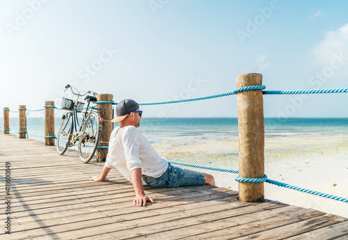 Obraz Portrait of relaxing man dressed in light summer clothes and sunglasses sitting and enjoying time and beach view on wooden pier.Careless vacation in tropical countries concept image. Zanzibar,Tanzania - fototapety do salonu