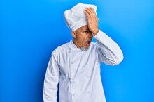 Middle Age Grey-haired Man Wearing Professional Cook Uniform And Hat Surprised With Hand On Head For Mistake, Remember Error. Forgot, Bad Memory Concept.