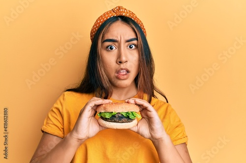 Young latin woman eating a tasty classic burger in shock face, looking skeptical Fototapeta