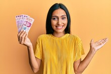 Young Brunette Woman Holding 50 Mexican Pesos Banknotes Celebrating Achievement With Happy Smile And Winner Expression With Raised Hand