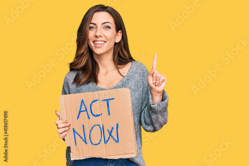 Young brunette woman holding act now banner surprised with an idea or question p Wallpaper Mural